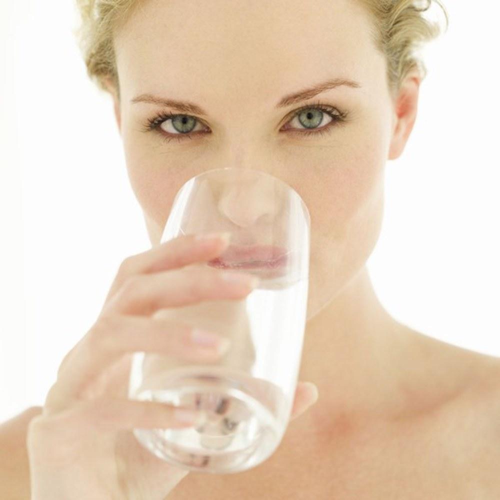photo d'une femme qui boit un verre d'eau. L'hydratation est le premier secret de la beauté.