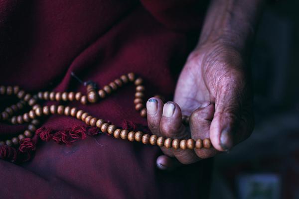 Gros plan sur la main d'un moine en train de prier avec un chapelet en bois, Tibet, Lhatse, extrait du livre 56000 kilomètres