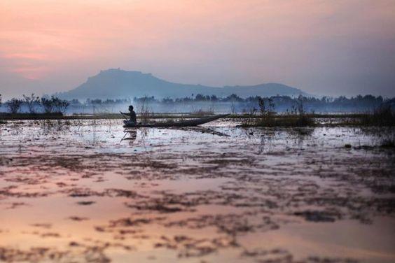 photo d'un homme sur une barque dans un lac du Cachemire en Inde, Srinagar, au coucher du soleil, extrait du livre 56000 kilomètres de Kares Leroy