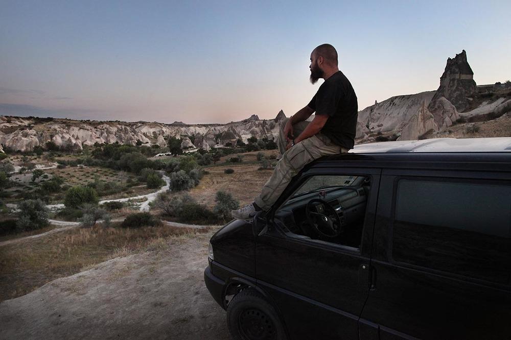 photo de Kares Le Roy assis sur son van, face à l'immensité de ce monde