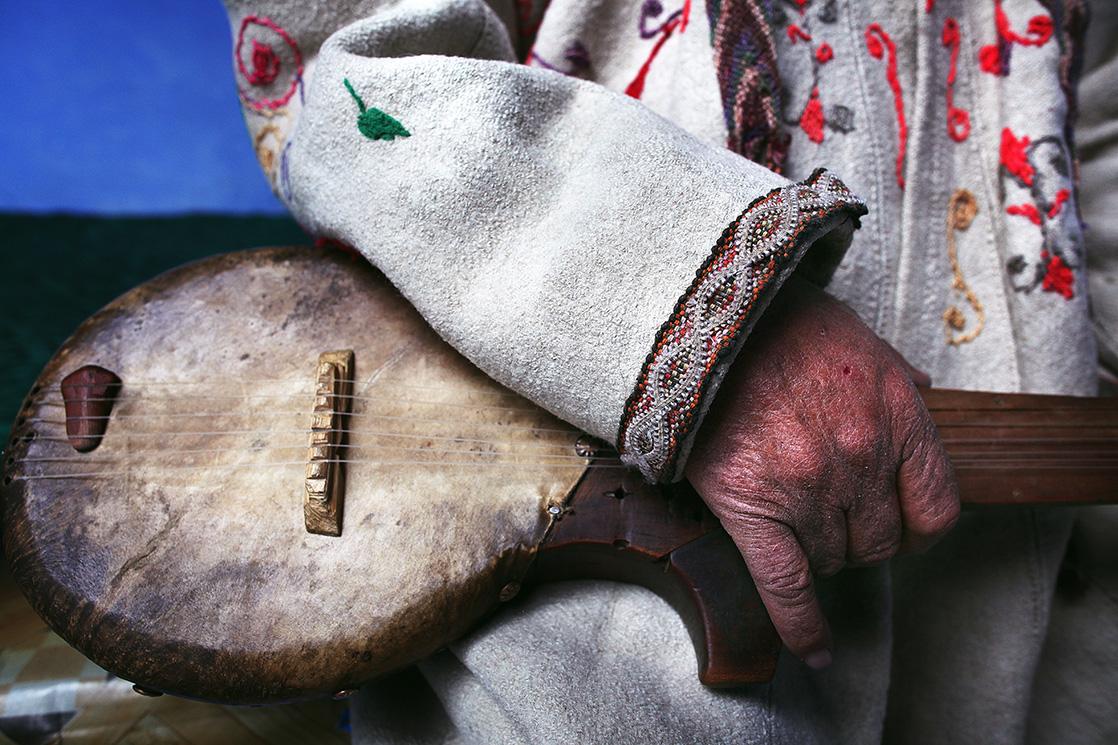 Gros plan sur une main tenue une guitare traditionnelle de la tribu des tadjik au Tadjikistan, extrait du livre Ashayer, nomades