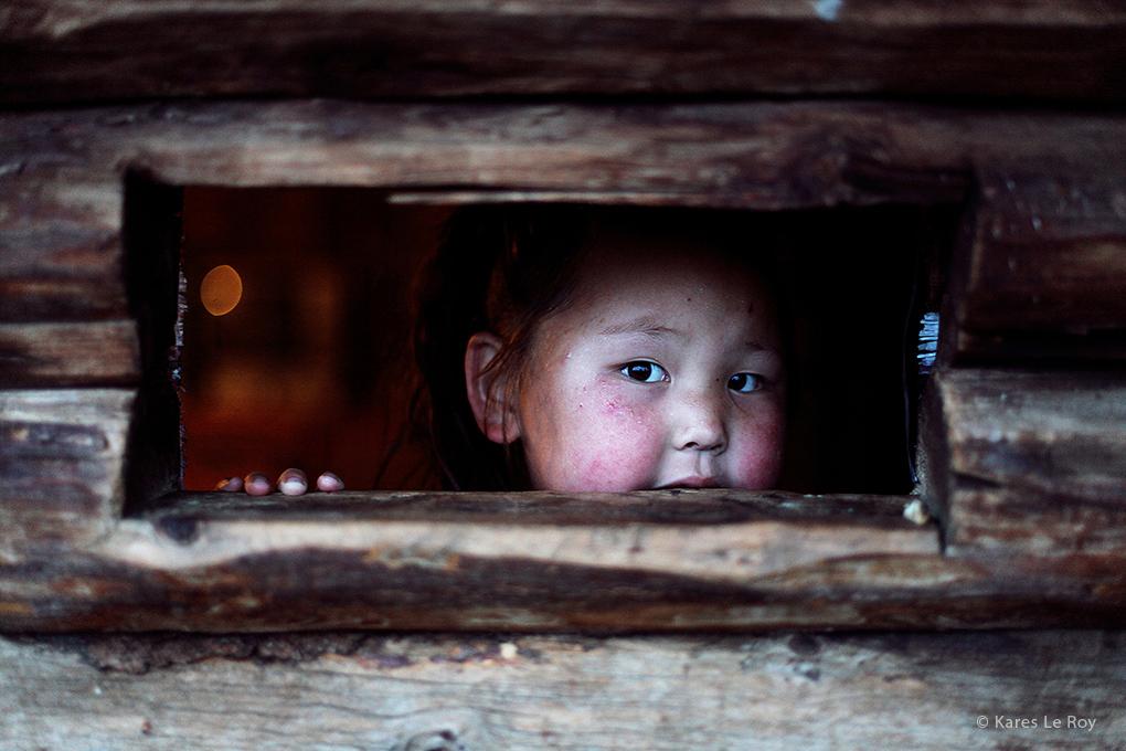 Portrait d'une petite fille qui se cache derrière une porte, extrait du livre 56000 kilomètres de Kares Leroy, Mongolie, Khövsgöl, tribu des Tsaatan