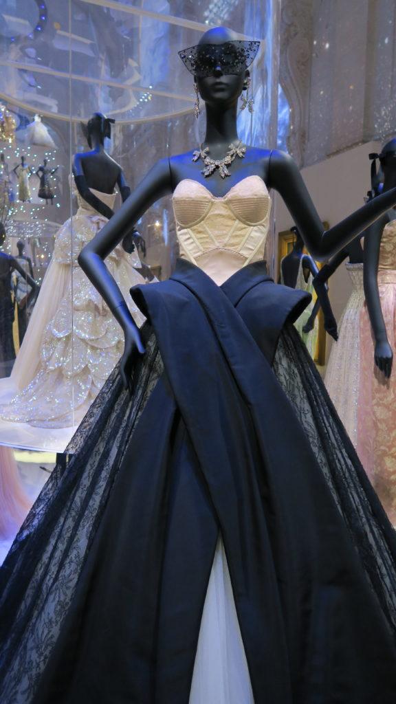 mannequin portant un bustier en soie, une jupe noire et un masque en dentelle Dior