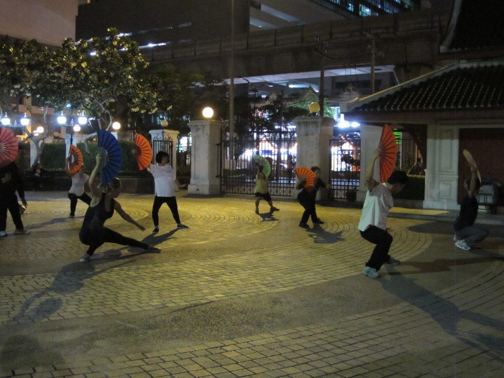 Entrainement d'un art martial qui se pratique avec un éventail, dans un parc en plein centre de Bangkok