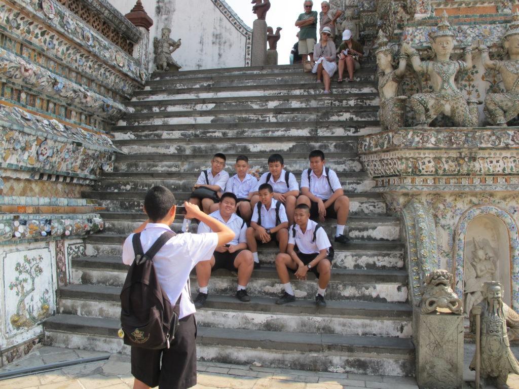 Des étudiants se prennent en photo sur les marches du temple Wat Arun