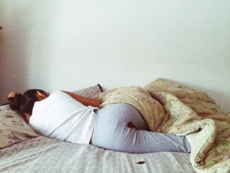 picture of Rupi Kaur in her bed, with period blood on her pants and on her sheet