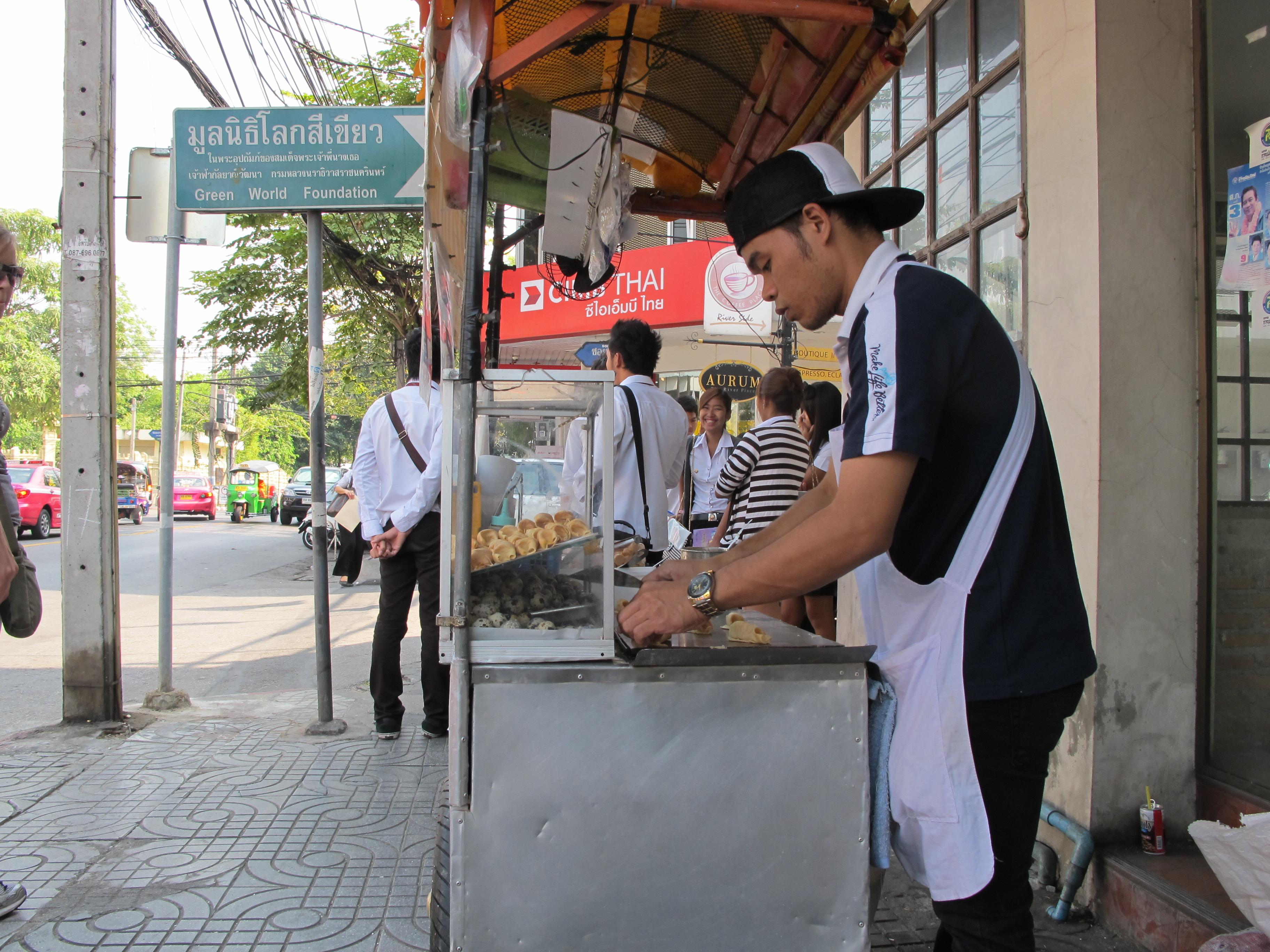 photo d'un jeune homme qui cuisine dans les rues de Bangkok